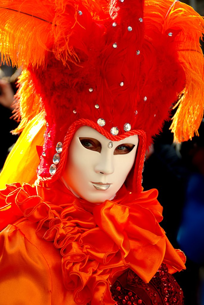 A festival-goer dons a feathery mask for Carnival